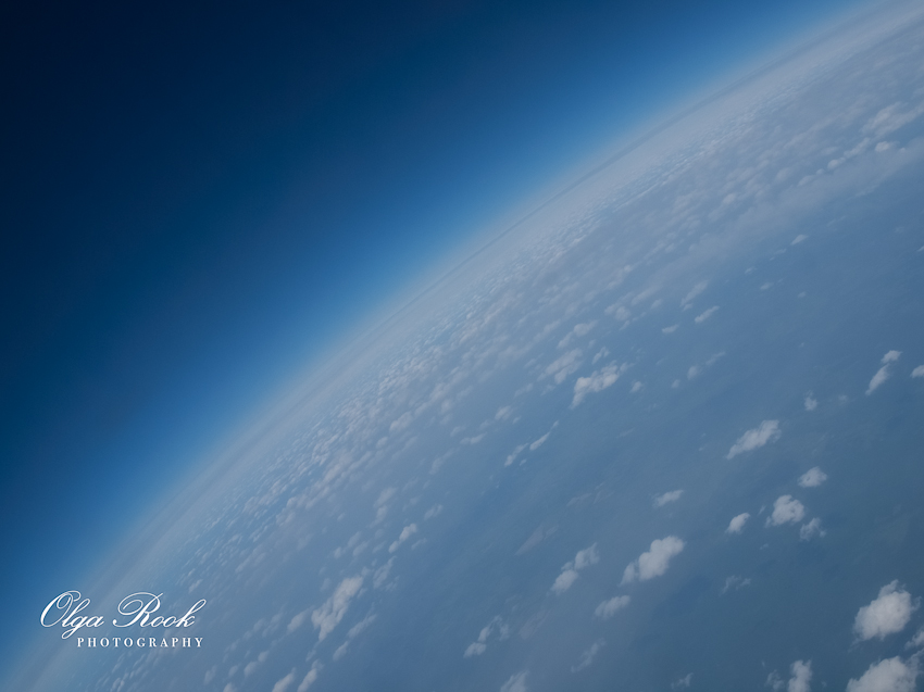 An aerial photograph: intens blue atmosphere above the Earth. The Earch can be seen at a diagonal angle and with rounded sides. That makes you think the photo was taken from a space ship.